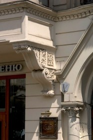 Просп. Шевченка, 21. Фрагмент фасаду в рівні І-го пов. Ліпний кронштейн еркеру (зліва), фрагмент вхідного порталу справа.