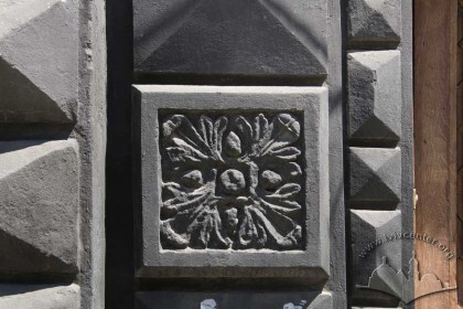 Pl. Rynok, 4. A rosette bass-relief on a rusticated pilaster