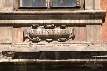 Пл. Ринок, 23. Напис на латині вирізьблений у камені. Розміщення — під вікном ІІ-го поверху  головного фасаду