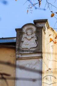 Вул. Лисенка, 12. Герб скраю північного фасаду, вирізьблений з білого каменю