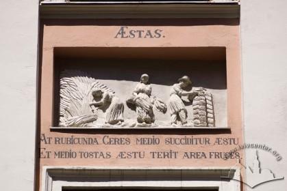 """Вул. Вірменська, 23. Рельєф над вікном 2 поверху (друге зліва) """"Літо. Жовтогарячу в жарінь серпом підтинають Цереру і на токах у жарінь сухе обмолочують збіжжя""""."""