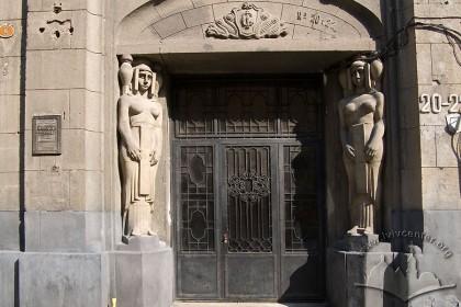 Вул. Гнатюка 20-22. Вхідний портал з металевими пізньосецесійними дверима, фланкований двома скульптурами єгиптянок авторства З. Курчинського.