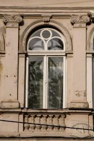 Вул. Галицька, 1. Вид на вікно ІІ-го поверху зі столяркою в стилі історизму, профільованими архівольтами, оточене з боків пілястрами з іонічними капітелями