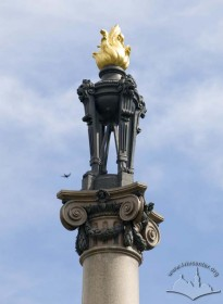 The flaming torch on top of the column