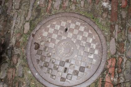 """Вул. Листопадового чину, 26. Давній каналізаційний люк із підписом """"Lwów W. Podhorodecki"""" у подвір'ї"""