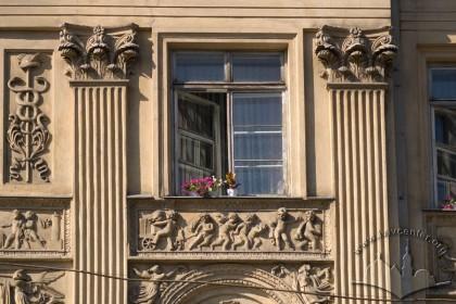 Просп. Свободи, 1-3. Фрагмент фасаду в рівні ІІІ-го пов. із канельованими пілястрами великого ордеру обабіч вікна та характерним для ампіру скульптурним фризом під ним