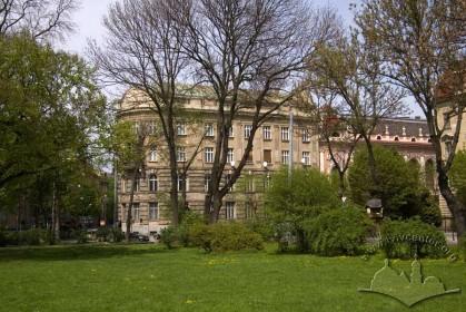 Вул. Листопадового чину, 8. Вид на південно-східний фасад будинку крізь дерева скраю парку ім. І. Франка