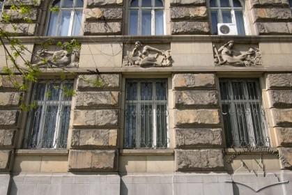 Вул. Листопадового чину, 8. Вікна 1-го поверху з рельєфними вставками зверху, з уособленнями сільського господарства, залізниці та видобутку корисних копалин