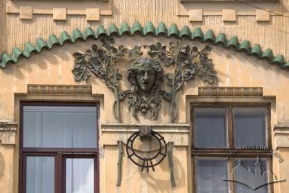 Вул. Руставелі, 8-8а. Горельєф з маскароном і гілками каштану між вікнами 2-го поверху над входом до будинку