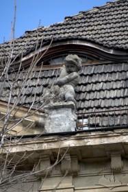 Вул. Левицького, 15. Фігура путті з рогом достатку над карнизом