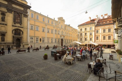 Pl. Yavorskoho. On the place occupied by tables, monument to hetman Stanisław Jabłonowski used to stand. On the background, the former Jesuit church and collegium on vul. Teatralna